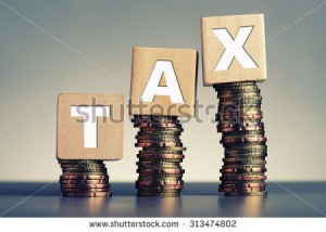 stock-photo-tax-concept-with-wooden-block-on-stacked-coins-313474802